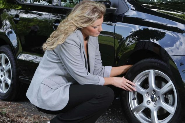 A lady checking her tyres before she sets off on holiday