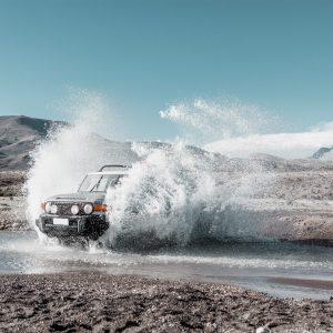 An Off-Road Vehicle Drives through Water with a Mountainous Backdrop