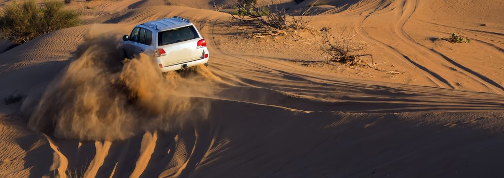 A white off-road vehicle driving in a desert.