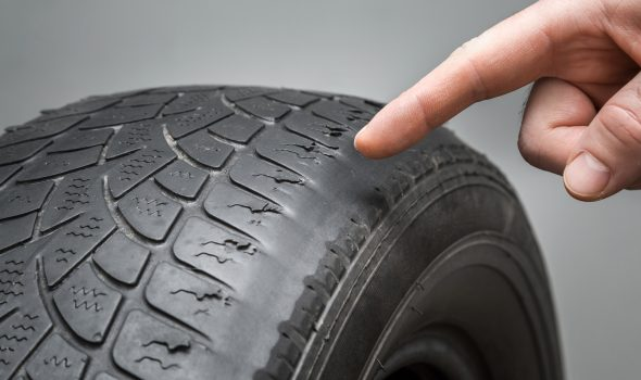 A hand pointing to a tyre to show worn tread