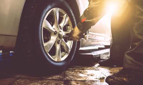 Mechanic changing tyre with spanner