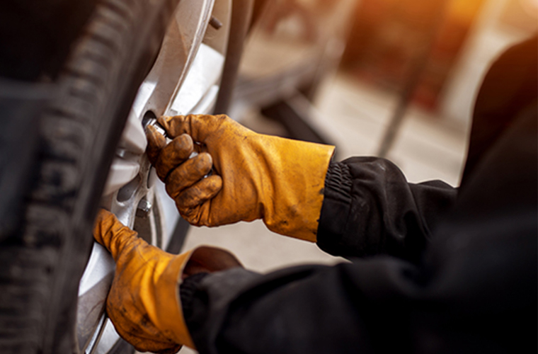 A close-up of a mechanic's hands checking the tyre pressure of a car