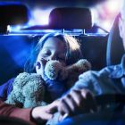 A child sleeping in the back of a car while her dad drives at night