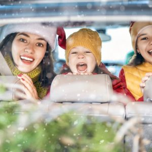 3 children sat in a car with a Christmas tree in the back seat