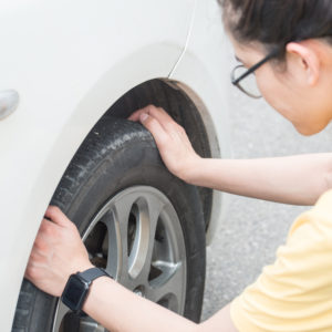 young woman touching and checking her car tyre. She worrying about somethings wrong with her wheel.