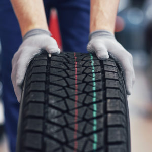 Closeup of mechanic hands pushing a black tire in the workshop.