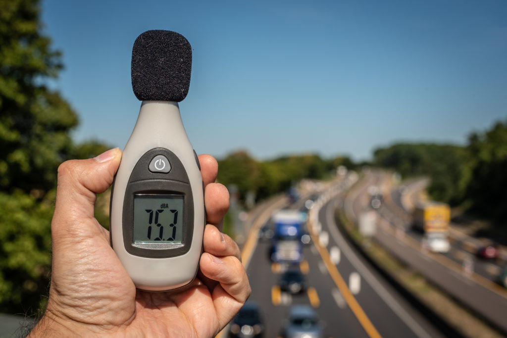 A man measuring the decibels (dB) of a motorway, whilst standing on a bridge.