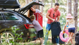 Family packing their car up, ready to go on a road trip out.