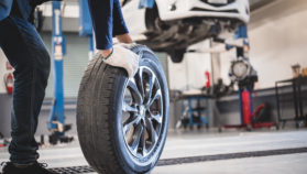 Male mechanic hold and rolling tire at repairing service garage background. Technician man replacing winter and summer tyre for safety road trip. Transportation and automotive maintenance concept